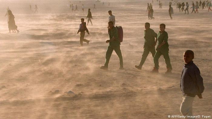 Photo: People walking through sand wind