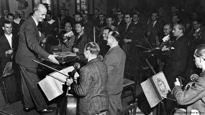 Surrounded by beaming faces, Wilhelm Furtwängler shakes hands with musicians
