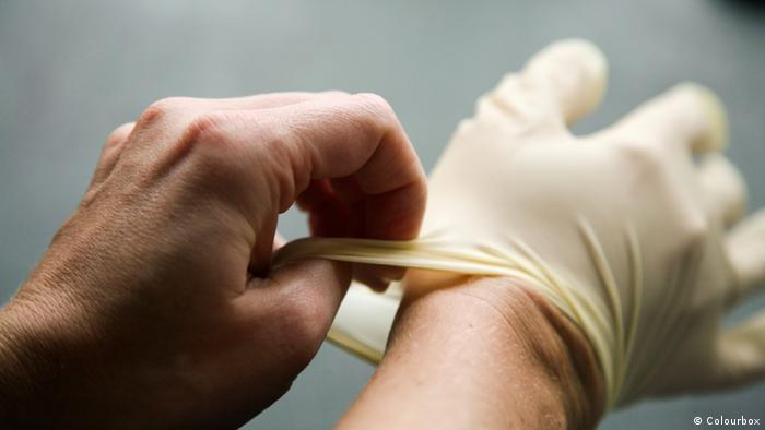 Person putting on a latex glove (Colourbox)