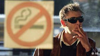 A man smokes a cigarette outside a building