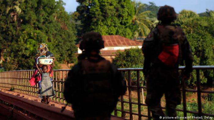 Zwei französische Soldaten grüßen im Mai 2014 eine Mutter und ihr Kind auf einer Brücke in der Stadt Bambari (Foto: AP)