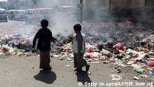 29.04.2015 *** Yemeni children walk past burning rubbish on a main street in the Yemeni capital, Sanaa, on April 29, 2015. AFP PHOTO / MOHAMMED HUWAIS (Photo credit should read MOHAMMED HUWAIS/AFP/Getty Images)