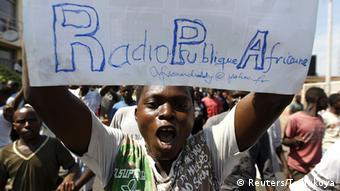 A protester carries a placard urging the government to re-open their local Radio Publique Africaine (RPA). Photo: REUTERS/Thomas Mukoya