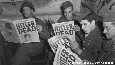 Allied soldiers read the newspaper announcing Hitler's death (picture alliance/Everett Collection)