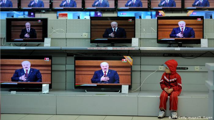 Ребенок смотрит на телевизоры в магазине, на экране которых выступление Лукашенко
