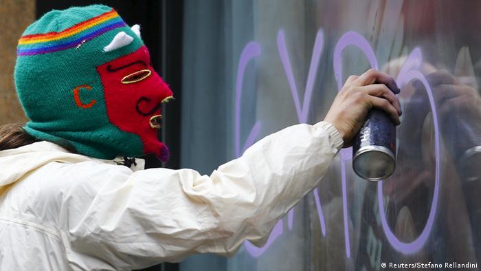 Vermummter besprüht eine Fensterscheibe