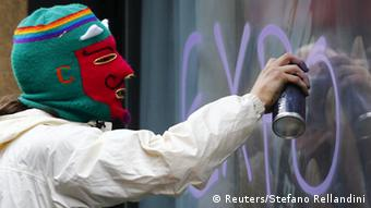 A protester spray paints a storefront