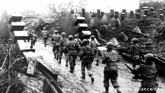 A picture of soldiers on a path with their guns out