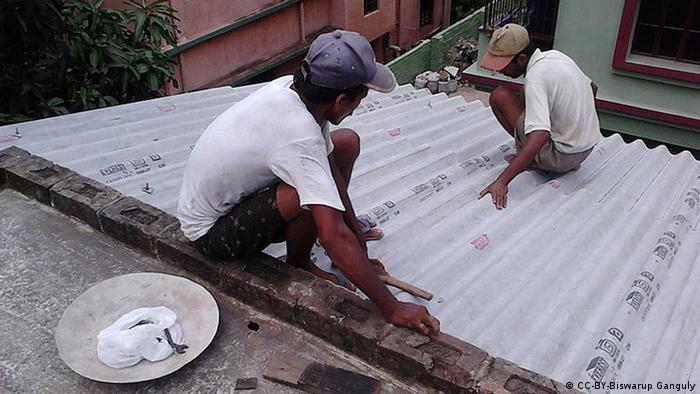 Indien Arbeiter decken Hausdach mit Asbest