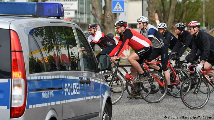 police car, bike riders (picture-alliance/dpa/A. Dedert)