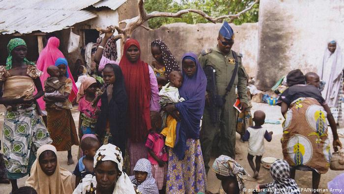 A group of women and girls inside a compound together with a Nigerian soldiers