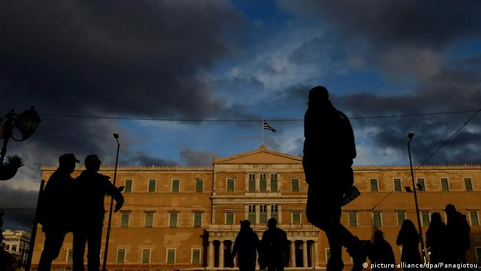 People walk in front of the Greek Parliament building in Athens under a dark, ominous sky