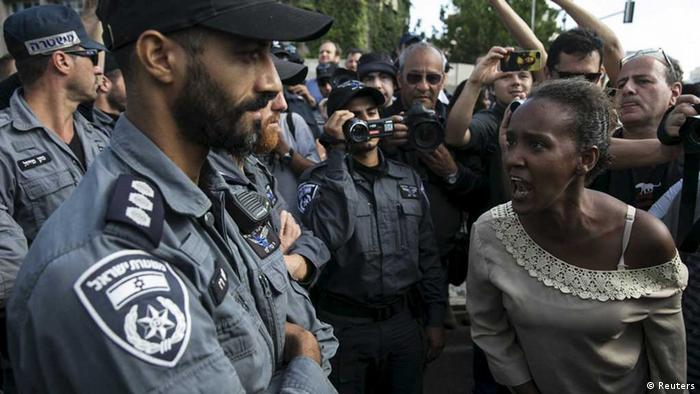 An Israeli-Ethiopian woman yells angrily at a policeman during a protest against police brutality and discrimination against Ethiopian Jews in 2015