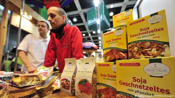 A salesman in Germany stands before a counter where boxes of soy-products are placed to attract customers