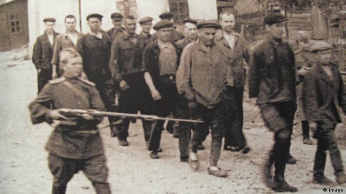 Заключенные под охраной на пути к месту работы