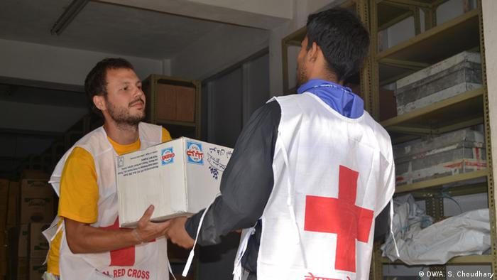 Red cross volunteers move relief material to deliver to remote areas