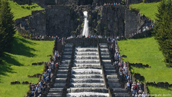 از بالای این شیب سنگی طبیعی۳۵۰ هزار لیتر آب به شکل آبشاری پلکانی با آهنگی موزون روان میشود و بازدیدکنندگان نیز میتوانند پای پیاده با آن همراه گردند. پارک سنگی «ویلهلمزهوهه» در شهر کاسل در سال ۲۰۱۳ به عنوان میراث جهانی یونسکو شناخته شد. این باغ که اثری هنری است با آبشار پلکانیاش و مجسمه هرکول و قصری که در بلندی آن قرار دارد، در آغاز قرن ۱۸ در این مکان ساخته شد.