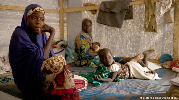 A young Nigerian girl with other refugees in a tent in a Chadian refugee camp
