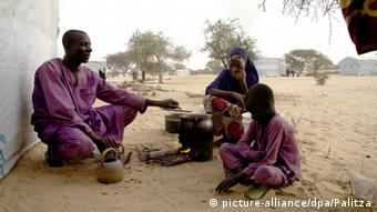 A Nigerian father and his children prepare a meal in a refugee camp