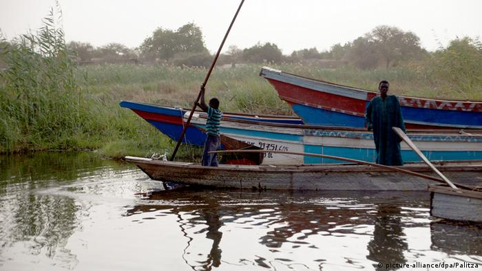 Chadian refugees use wooden canoes to cross Lake Chad.