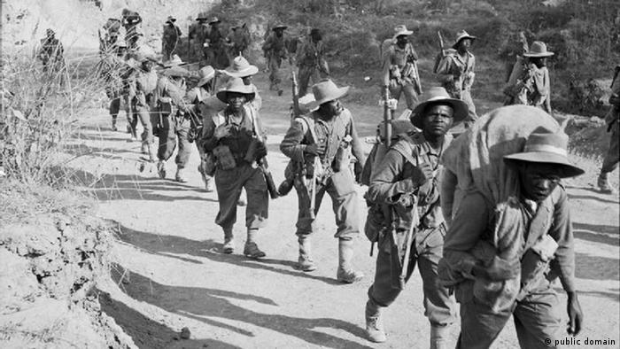 African soldiers walk along a dirt road in Burma