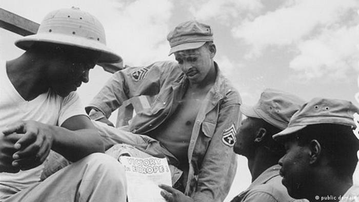 African soldiers in Burma with a copy of President Truman's proclamation of peace in Europe