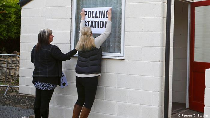 Two women sticking up a 'polling station' sign