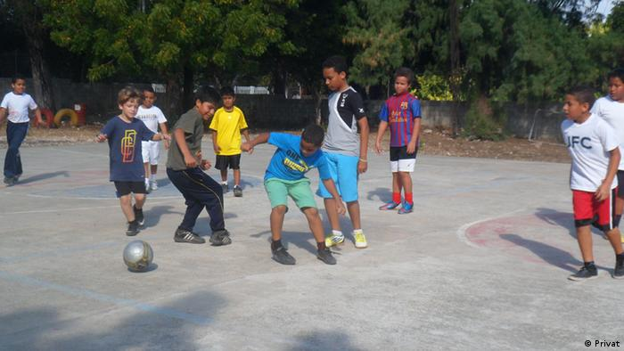 Kids play on a hard court in the Dominican Republic