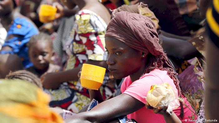 A woman refugee drinks from a cup at a refugee camp in Nigeria.