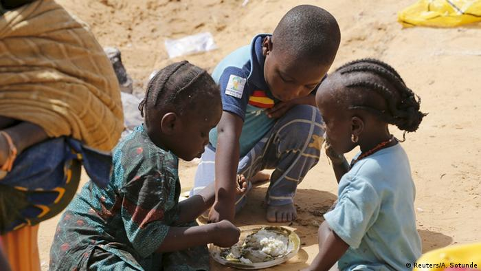 Three young children sit on the ground sharing a plate of food (Photo: Reuters)