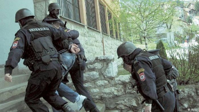 Police drag a suspected Islamist extremist up stairs