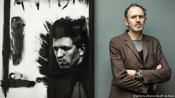 Anton Corbijn poses in front of a self portrait in the Gemeente Museum in The Hague