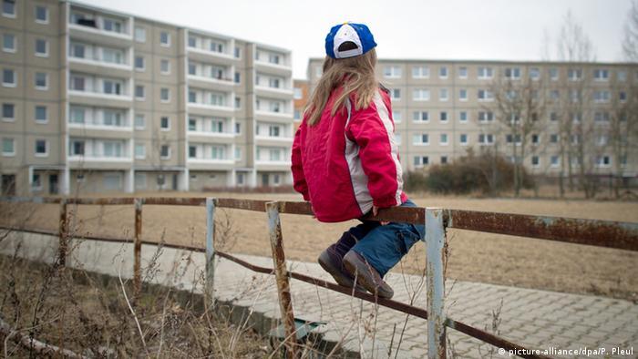 Kid sitting next to a housing complex