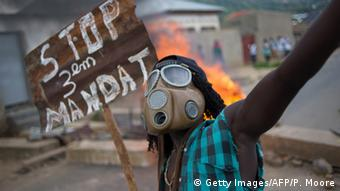 A Burundian protester wearing a gas mask and holding a sign that reads Stop the third mandate