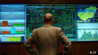 An engineer looks at the screens of a natural gas operation center
