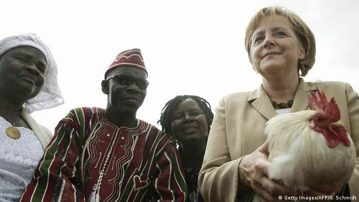 Angela Merkel holding a chicken in Liberia (Getty Images/AFP/A. Schmidt)