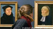 Wittenberg (Sachsen-Anhalt): Zwei Cranach-Gemälde, die Martin Luther und seine Frau Katharina von Bora zeigen, betrachtet am 04.03.2003 eine Frau in der neuen Dauerausstellung des sanierten und teilweise neu gestalteten Lutherhauses in Wittenberg. Die Exposition der zum UNESCO-Weltkulturerbe gehörenden Lutherhalle, die am 06.03.2003 eröffnet wird, zeigt neben den historischen originalen Gegenständen von Luther auch viele neu angkaufte Kunstwerke und Gegenstände aus der Lutherzeit. Das ehemalige Wohnhaus des Reformators Martin Luther (1483-1546) war zuvor innerhalb von rund zwei Jahren für fünf Millionen Euro umfassend saniert und im Oktober 2002 wieder eröffnet worden. (HAL02-050303)