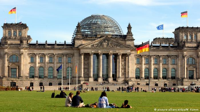 The German Reichstag with German and European flags. People are sitting on the lawn.(picture-alliance/dpa/W. Kumm)