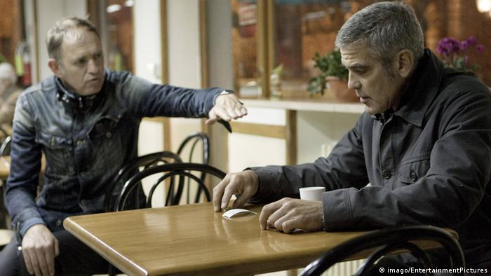 Two men sit at a table (The American mit George Clooney)