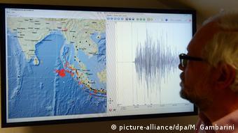 Silhueta de homem diante de monitor de vídeo com imagem de satélite da região da Indonésia e gráfico de sismógrafo