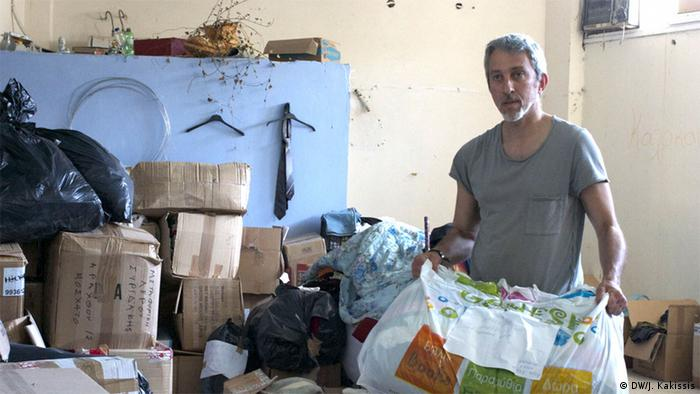 Panos Rozakisstands among bags of donated clothes