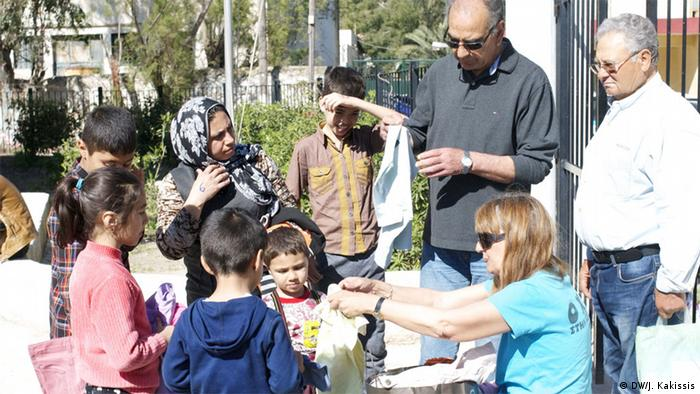People hand out clothes to Afghan refugees
