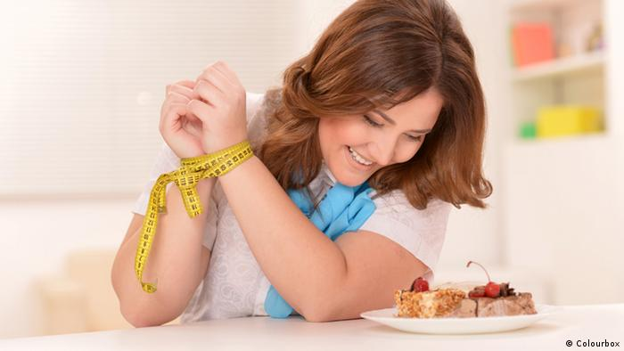 A woman laughing alone with two pieces of cake while her hands are tied with a measuring tape. (Colourbox)
