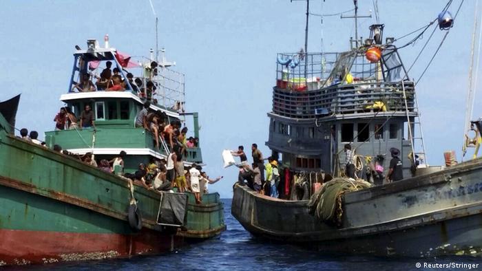 Thailändische Fischer auf einem Boot reichen Lebensmittel an Flüchtlinge (Foto: Reuters/Stringer)