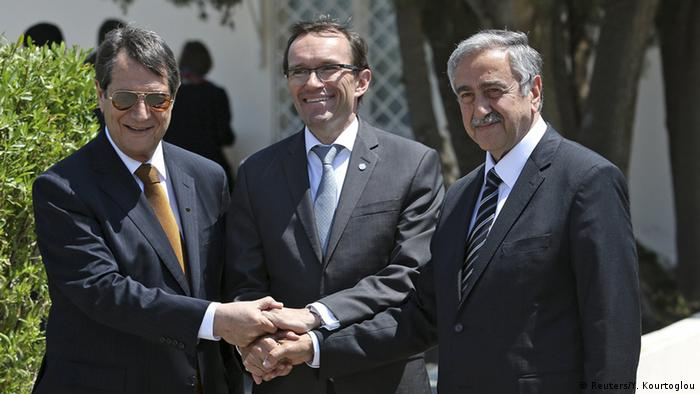Greek Cypriot leader and Cyprus President Nicos Anastasiades (L) shakes hands with Turkish Cypriot leader Mustafa Akinci (R) and UN envoy Espen Barth Eide (C) while a UN peacekeeper looks on at United Nations offices in the buffer zone of Nicosia airport, May 15, 2015 (Photo: REUTERS/Yiannis Kourtoglou)