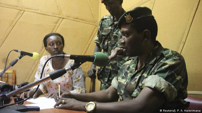 Burundian army general Godefroid Niyombare reads infront of a microphone inside a radio station in Bujumbura.