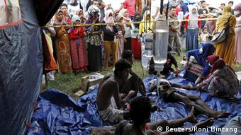 Rohingya and Bangladeshi migrants who arrived in Indonesia by boat receive medical assistance at an aid tent as local residence look on in Kuala Langsa, in Indonesia's Aceh Province May 15, 2015 (Photo: REUTERS/Roni Bintang)