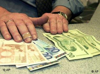 A bank teller with euro and dollar notes