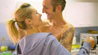 Szene aus Sommer vorm Balkon: Frau und Mann umarmen sich