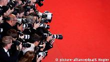 Un grupo de fotógrafos junto a una alfombra roja.